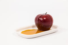 Red apple with drops of honey on white plate with honey isolated Royalty Free Stock Image