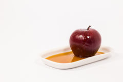 Red apple with drops of honey on white plate with honey isolated Stock Photography