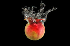 Red apple falling into water Stock Photo
