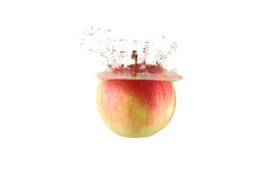 Red apple falling into water Royalty Free Stock Image