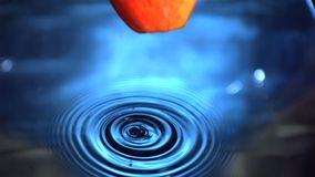 Red apple falling into water with drops Royalty Free Stock Photography