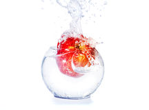 Red apple falls in water Royalty Free Stock Photo