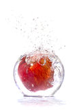 Red apple falls in water Royalty Free Stock Image