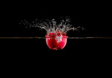 Red apple falls into water on dark background Stock Images