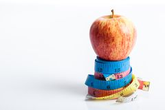 Red apple on four color measuring tapes Royalty Free Stock Photo