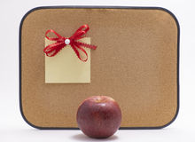 Red apple in front of bulletin board with reminder note Royalty Free Stock Images