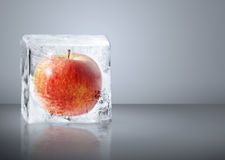 Red Apple frozen inside big ice. Red Apple frozen inside  big ice ice cube with water drops Royalty Free Stock Photography