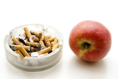 Red apple with full ashtray Royalty Free Stock Photography