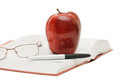 Red apple and glasses on the book Stock Images