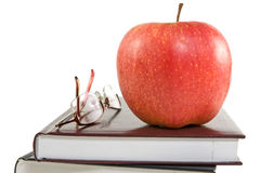 Red apple and glasses on the books Stock Image