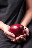 A Red apple glive as a present. A red and juicy apple offered from a girl hand Stock Photo