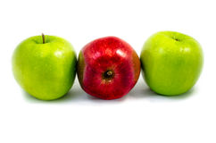 A red apple among green apple on the right and left isolated on Royalty Free Stock Photography
