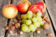 The red apple and green grapes and nuts on wooden background. Autumn fruits - the red apple and green grapes, close up. horizontal Royalty Free Stock Photo