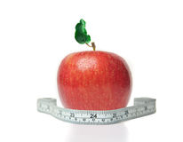 Red apple with green leaf and measuring tape Royalty Free Stock Images