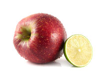 Red apple with half of lime on a white. Big red apple with half of lime on a white background (water drops). Fresh diet fruit. Healthy fruit with vitamins Royalty Free Stock Photos