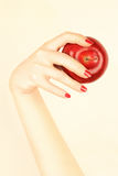 Red apple in the hand. Red apple in the beautiful hand with red nails Stock Image