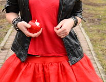 A red apple in a hand of a girl in a red dress Royalty Free Stock Images