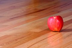 Red Apple on Hardwood Floor Stock Photo