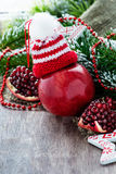 Red apple in hat and pomegranate with festive decorations Stock Image