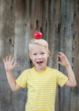 Red apple on the head of a child. Boy and apples in the garden stock image