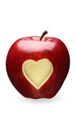 Red apple with heart. Red apple with a heart symbol against white background Stock Image