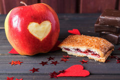 Red apple with heart carved on, cherry pie and chocolate bars decorated with little red stars St.Valentine's Day Royalty Free Stock Photos