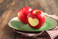Red apple with a heart shaped cut-out. On plate Stock Photo