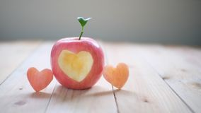 Red apple with a heart shaped cut-out royalty free stock image