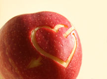 Red apple with heart symbol. Red apple with heart and arrow symbol stock photography