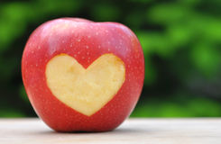 Red apple with heart symbol on wooden table over nature backgrou Royalty Free Stock Images