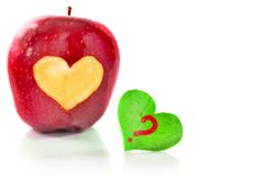 Red apple and the heart which is cut out from apple. Red apple and the green heart with the question mark which is cut out from apple. A close up, selective Royalty Free Stock Photos