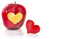 Red apple and the heart which is cut out from apple. A close up, selective focus, it is isolated on white Royalty Free Stock Images