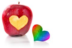 Red apple and the iridescent heart which is cut out from apple. A close up, selective focus, it is isolated on white Stock Image