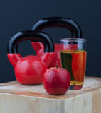 Red apple, juice, and kettlebells on chopping board Stock Image