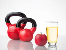 Red apple, juice, and kettlebells on reflective surface Stock Images