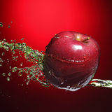 Red apple in juice stream Stock Photos