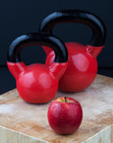 Red apple and kettlebells on chopping board.  Stock Image