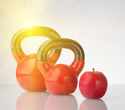 Red apple and kettlebells on reflective surface Royalty Free Stock Images