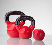 Red apple and kettlebells on reflective surface Royalty Free Stock Photos