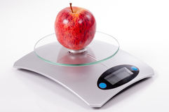 Red apple on kitchen scale Royalty Free Stock Photography