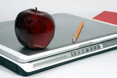 Red apple on laptop with book and pencil. Red apple on a closed laptoop whith pencil and red book Royalty Free Stock Photos