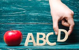 Red apple and letters of the ABCD. The hand puts the letter D to the others in a row. Apple for the teacher. Concept of education,. Primary school, student Royalty Free Stock Images