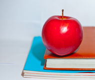Red apple lies on textbooks. And waiting when he will eat Stock Photo
