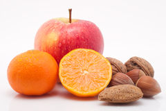 Red apple, mandarins with drops and nuts on white Royalty Free Stock Photography