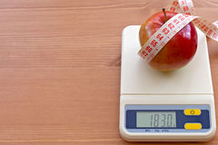 Red apple with measure tape on electronic scale, d. Iet concept stock photos