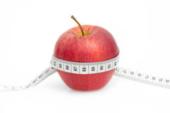Red Apple with measure tape on white. Background Royalty Free Stock Photos