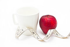 Red apple and measure tape with white ceramic glass. Royalty Free Stock Photo