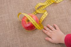 Red apple with a measurement  tape on it Royalty Free Stock Photos