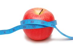 Red apple and measuring tape. Isolated on white Stock Photos