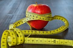 Red apple with measuring tape on board. Fruit as a healthy way of life. Weight reduction diet and workout Royalty Free Stock Photography